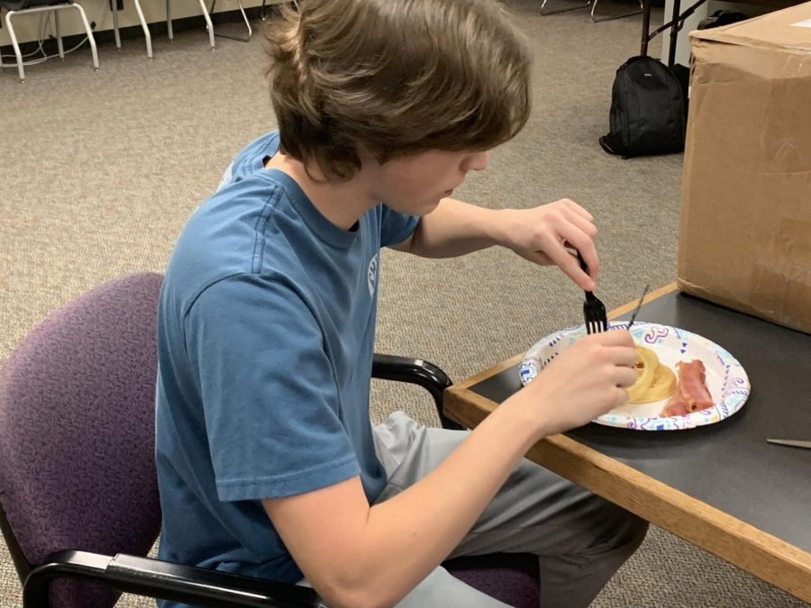 Sophomore Nathan Hutcheson enjoys bacon and waffles during lunch in the newspaper room.
