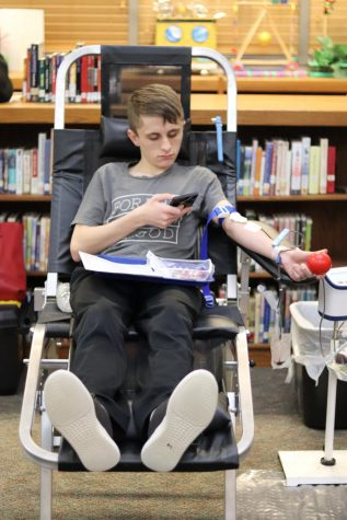 Senior Tommy Tye looks at his phone while he gives blood during the February Blood Drive. Over 50 students signed up to give blood to help people in need.