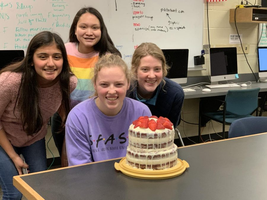 Newspaper staff members Nistha Neupane(10), Cadence Pov(11), Alex Norton(11), and Delia Tuttlebee(11) pose around a cake that Alex Norton made for the staff. Alex often brings different homemade treats to the newspaper classroom for her friends.