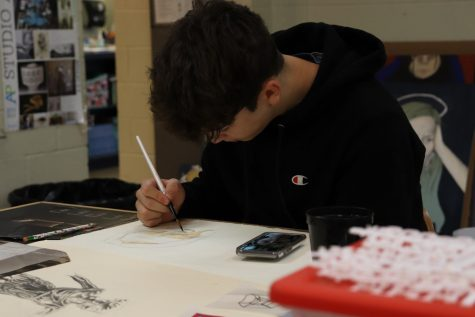 Senior Gabe Smith works on his art project in Advanced Art during first period. Gabe Smith is a member of National Art Society and frequently visits the art classroom to work on his artwork.