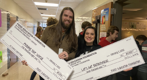 "Science teachers Thomas Strawn and Shelby Strawn hold the ""checks"" they received from the Pleasant Grove Educational Foundation for grants to the science department."