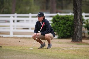 Junior Golfer Noah Neal squats during the New Haven Golf Tournament over the weekend.