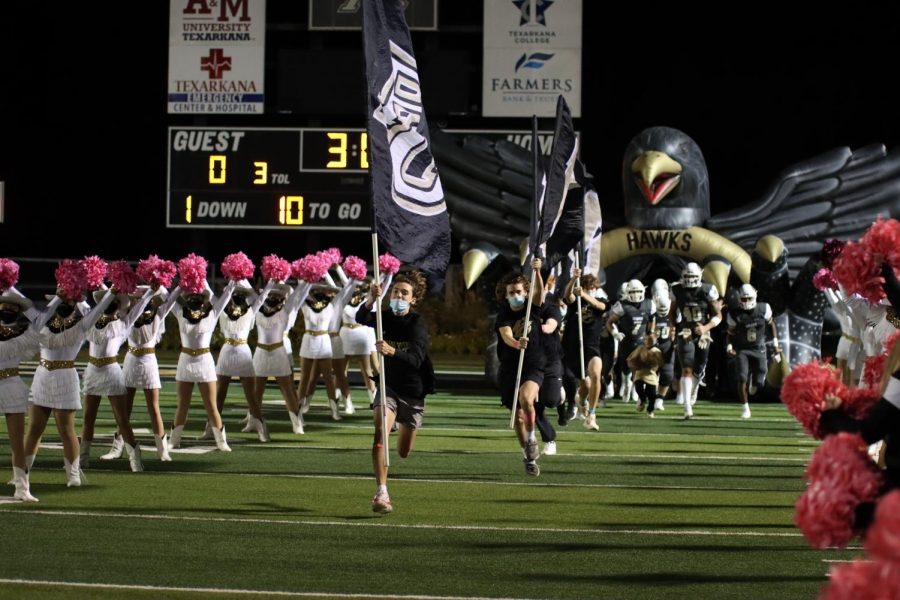 Flag runners running the Pleasant Grove flags before the game.